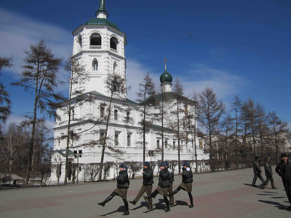 A troop of young girls marching through the square in Irkutsk.